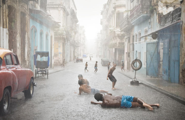 <p>A summertime rain shower is very much appreciated by the children of Havana, Cuba.</p>