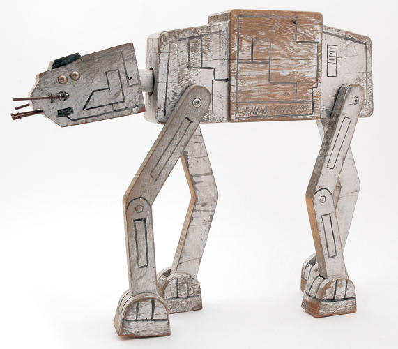 <p>A friend picked this up at a flea market for $10 more than 20 years ago. To me, it's a piece of folk art. My theory is that some kid really wanted an Imperial Walker (AT-AT) but dad couldn't afford it; so he went into his woodshop, carved this with moving joints and nails for the chin guns, and then drilled two holes on top for action figures. Awesome piece!</p>