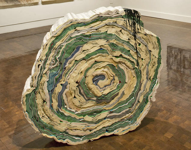 <p>Jacqueline Rush Lee scrambles books' formal arrangement to create what she calls &quot;residual&quot; sculptures. Installed at the Honolulu Museum of Art, Hawaii. &quot;Island&quot; was assembled from telephone books using screws and decorated with found and applied inks.</p>