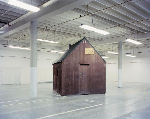 <p>After FBI agents captured Ted Kaczynski at his remote cabin outside Lincoln, Montana, in 1996, the cabin was shipped across the country to be used as evidence in his trial. Barnes managed to finagle access to the building where it was being stored: the stark, windowless warehouse in Sacramento you see here.</p>