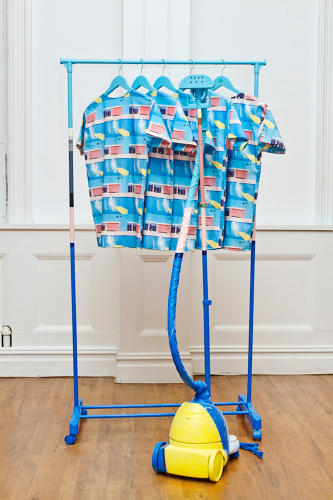 <p>David Hockney's iconic 1967 painting, <em>A Big Splash</em>, makes an appearance in a rack of T-shirts and accompanying steamer.</p>