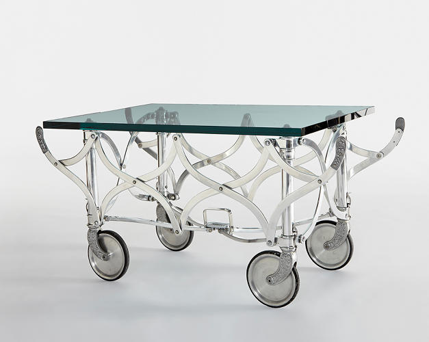 <p>Polished aluminum, steel, glass.<br /> Casket carrier manufactured by Champion Chemical Company, USA, together with after-market custom glass table top. (Estimate: $6,000–$8,000)</p>