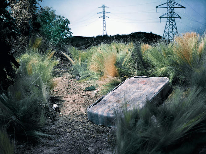 <p>A haunting image from the project--a blood-stained mattress sits below a power line.</p>