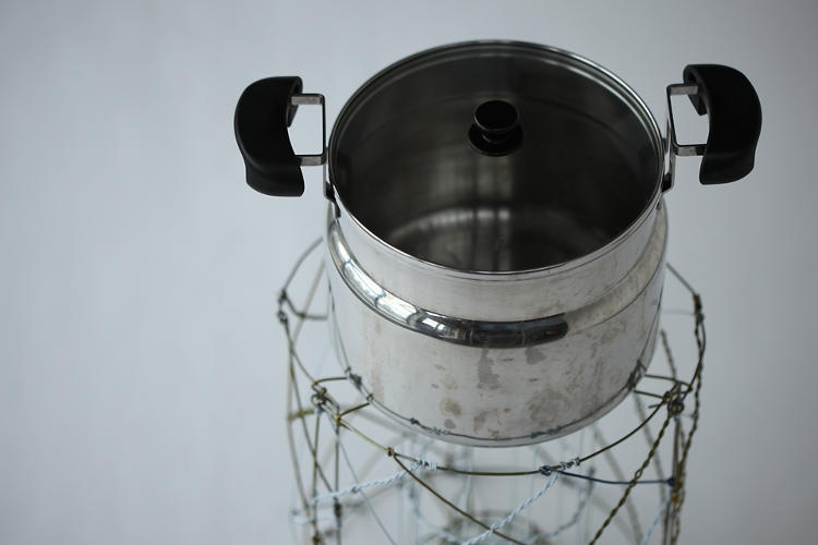 <p>The pot sits stop the wire structure.</p>