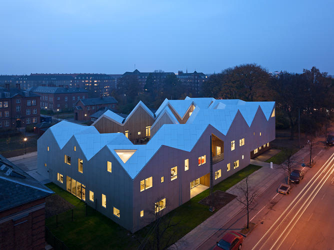 <p>Johannes Molander Pedersen of NORD Architects says his firm's Centre for Cancer and Health operates with a duality: a warm, inward-facing, wood-clad yard, and an iconographic aluminum facade which changes with the light.</p>
