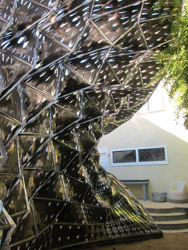 <p>When exposed to heat, the perforated pieces curl, increasing air flow through the structure.</p>