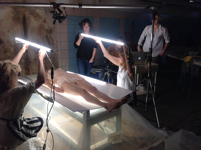 <p>A behind-the-scenes shot shows McRae's assistants holding fluorescent lights above the model.</p>