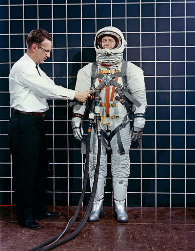 <p><strong>The Perfect Fit</strong><br /> Engineer Bill Peterson fits test pilot Bob Smyth in spacesuit A-3H-024 with the LEM Astronaut restraint harness during suit evaluation study.</p>