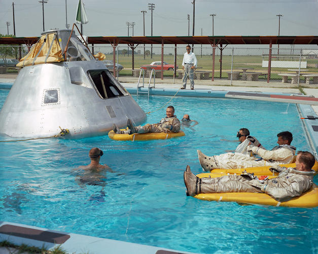 <p><strong>Chillaxing</strong><br /> Prime crew for the Apollo VII mission practice water egress procedures with full-scale boilerplate model of their spacecraft. In the water at right is Astronaut Edward H. White foreground and Astronaut Roger B. Chaffee. In raft near the spacecraft is Astronaut Virgil I. Grissom. NASA swimmers are in the water to assist in the practice session that took place at Ellington AFB, near the Manned Spacecraft Center, Houston.</p>