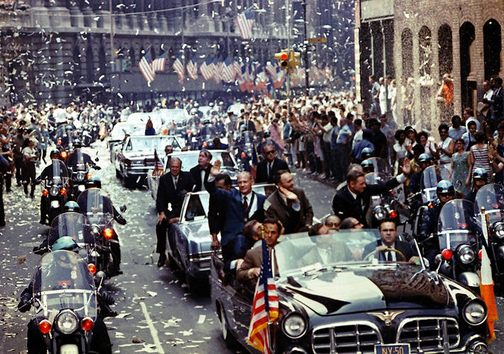 <p><strong>Ticker Tape Reception</strong><br /> New York City welcomes Apollo 11 crewmen in a showering of ticker tape down Broadway and Park Avenue in a parade termed as the largest in the city's history. Pictured in the lead car, from the right, are astronauts Neil A. Armstrong, commander; Michael Collins, command module pilot; and Edwin E. Aldrin Jr., lunar module pilot. The three astronauts teamed for the first manned lunar landing, on July 20, 1969. Credit: NASA Photo by Bill Taub.</p>