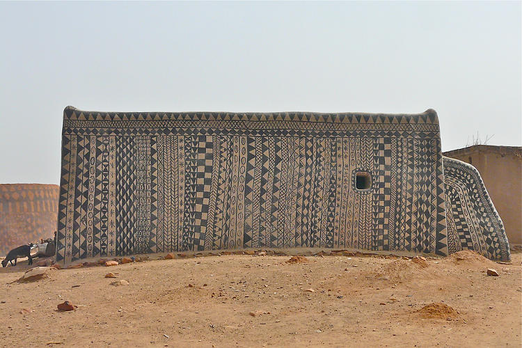 <p>Before the rainy season sets in, the women use locally-found materials to inscribe patterns and colors into the walls of the newly-constructed homes.</p>