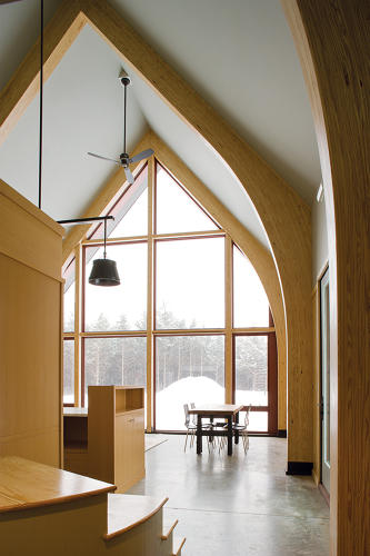 <p>The concrete floor provides thermal mass. The laminated pine beams stretch upward into a cathedral ceiling. Completed in 2010, this is the first certified Passive House in New York state.</p>