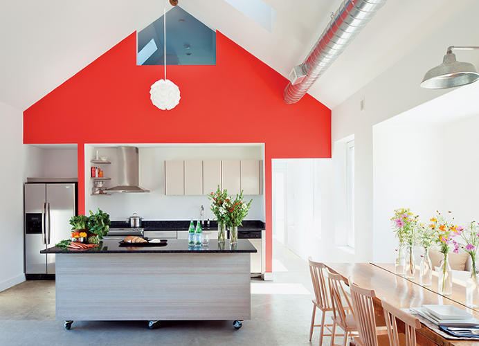 <p>The open layout promotes air circulation and allows for a simplified heating and cooling system, with a single exposed metal duct passing through the main living space. Here, the children's loft is visible through an opening above the kitchen.</p>