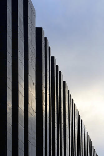 <p>Designed by Heneghan Peng Architects, the building consists of a series of basalt columns, irregularly spaced with glass panes fitted in between.</p>