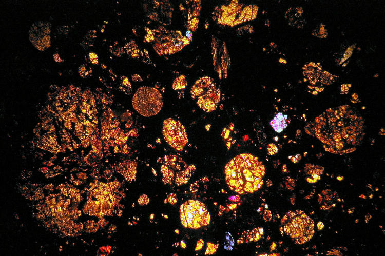 <p>Cracking open meteorites requires a rock saw with a diamond-coated blade. Scientists like Barton will grind a postage stamp-sized piece of the rock until it's thin enough for light to pass through and then glue the slice to a microscope slide for its photo shoot.</p>
