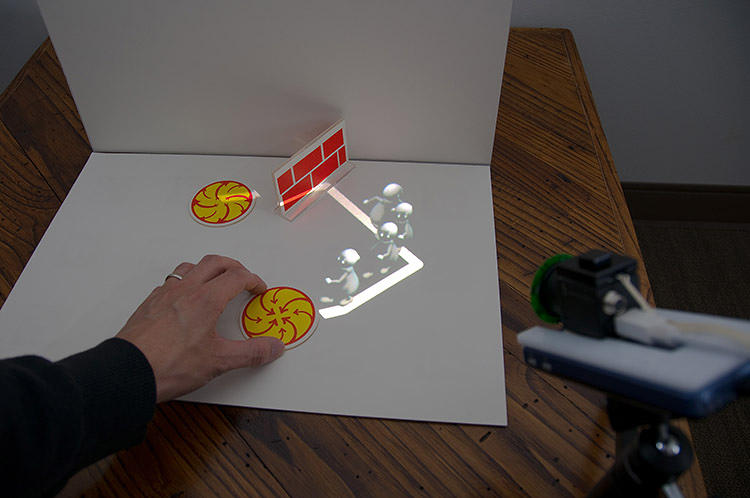 <p>Invisible computer-vision codes in the tangible pieces make the projected characters react to them. Here, the characters march away from a brick wall they can't pass through.</p>