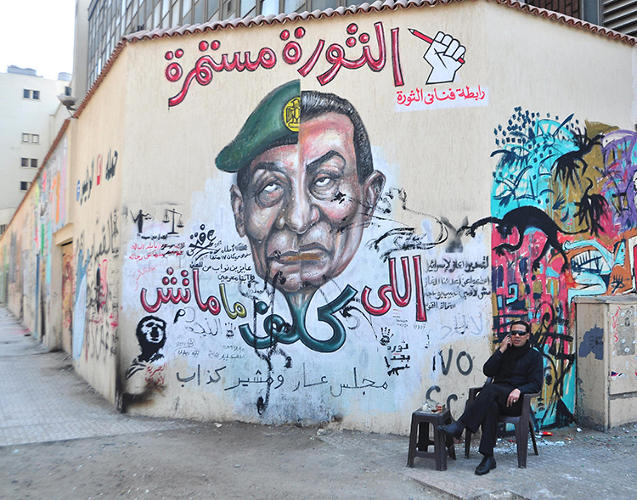 <p>&quot;In Egypt we have a saying: 'The one who bears children, doesn't die,' meaning that if you have kids, you live on through them. An artist called Omar Fathy created a mural to object to military rule after Mubarak's ousting, using a spinoff on that famous saying, but instead of the word meaning 'bears children' he replaced it with a word to mean 'delegate.' Because the two words rhyme in Arabic, it reflects the artists intent in exposing Tantawy's  loyalty to Mubarak (Tantawy was the head of the military at the time). The mural shows half of Mubarak and half of Tantawy's heads fused together to show they are one and the same.</p>