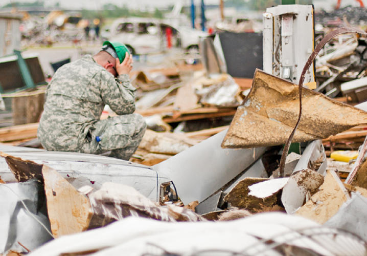 A veteran, helping with search and rescue, sits amongst the devastation the day after the tornado.
