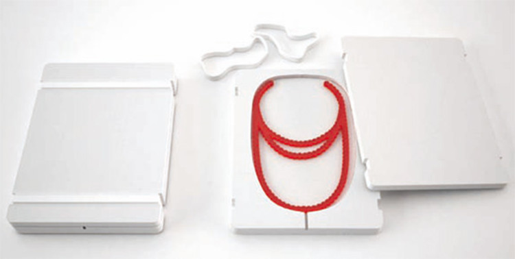byAMT's design, for a package containing an acrylic necklace. The two polystyrene boards are held together by white rubber bands.