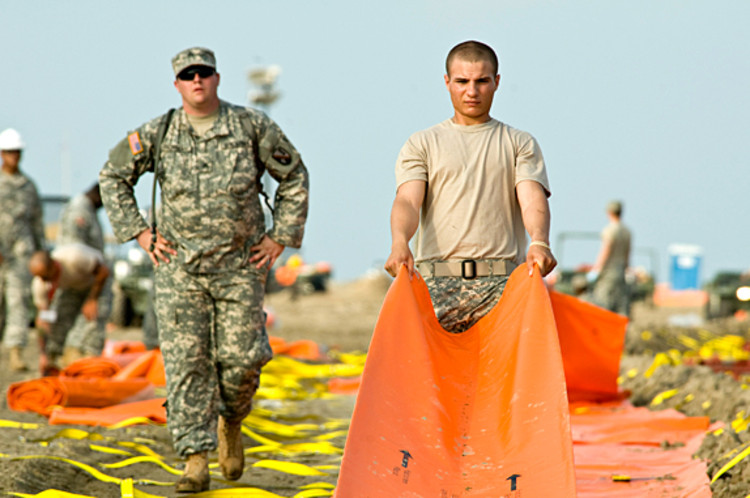 Soldiers work fast and hard to lay out miles of protective oil boom along the Grand Isle shoreline. They were working to break the previous night's record set by another crew in a running competition devised to motivate the troops.
