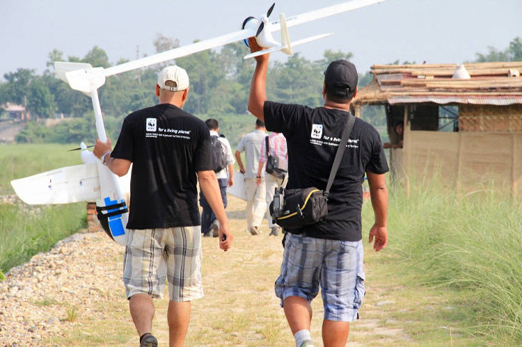 <p>WWF Nepal staff carrying drone to flight site</p>