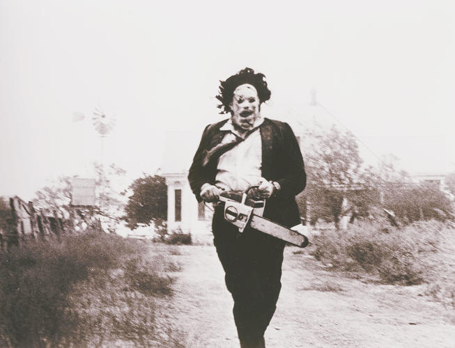 <p>Leatherface, played by Gunnar Hansen, runs from the house in <em>Texas Chainsaw Massacre</em>.</p>