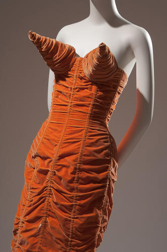 <p>Jean Paul Gaultier, orange shirred velvet dress with cone bust and back lacing, 1984, France. The Museum at FIT, P92.8.1.</p>