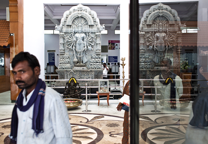 <p>Family members of the patients and other visitors walk past a HIndu God's statue in the waiting lounge of the Narayana Hrudayalaya in Bangalore, Karnataka, India.</p>