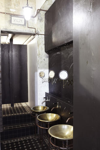 <p>The bathrooms are more straightforwardly steampunk, with copper-colored sinks and exposed plumbing punctuating the dark, buffed steel covering the walls.</p>