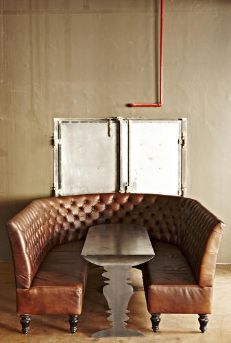 <p>Plush leather sofas, which sit at the rear of the shop, wrap around steel tables, creating more intimate gathering spaces in the otherwise cavernous shop.</p>