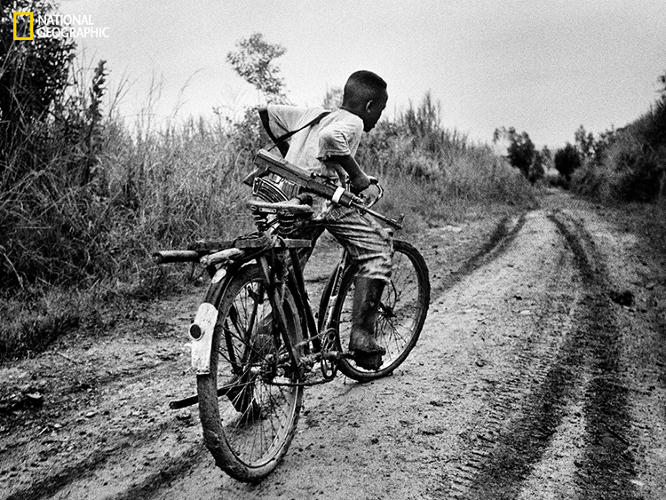 <p>Already a soldier, a boy with an assault rifle pedals to base camp during fighting in the Ituri region in 2003. Photographer Marcus Bleasdale says that of all of his images from the Congo, this one has provoked the most response from the public.</p>