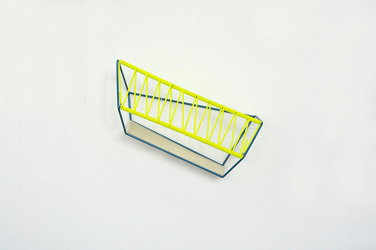 <p>In looks, the Quadrat is an oddity. A steel bar coiled and wrapped around with yellow rubber straps that appears to hold several different perspectives at once.</p>