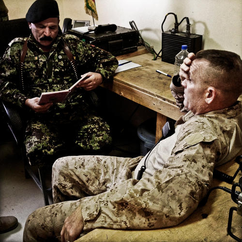 <p>Lt. Col. Phil Treglia stands by as Col. Muhammed Salwar of the Afghan National Army gets morning reports over the radio from the brigade's battalions, or &quot;kandaks.&quot;</p>