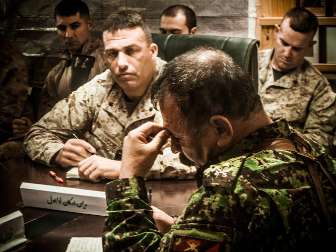 <p>Lt. Col. Douglas Luccio (left foreground) and Lt. Col. Phil Treglia (background) sit in on the Afghan officers' daily morning meeting at Camp Garmsir with ANA Col. Muhammed Salwar.</p>