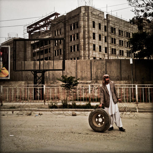<p>An Afghan standing in front of a construction site for a four-star hotel being built for the U.S. embassy in Kabul.</p>