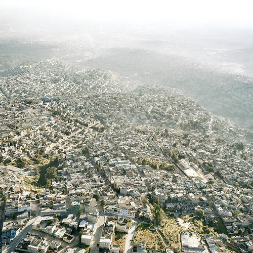 <p>As a relentless stream of people continue to move into the area looking for new opportunities, the sea of houses continues to spread, both in informal settlements and the giant cleared developments that Lopez depicts.</p>