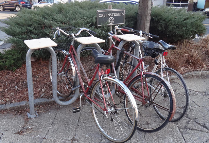 <p>Scraps of wood were tacked on the top of a bike rack to hold<br /> belongings while someone unlocks a bike.</p>