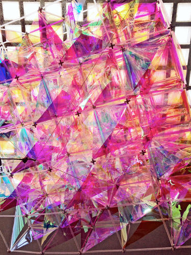 <p>3M (maker of the Post-it note) worked with Brooklyn-based design firm SO-IL to create a kite from 3M's Dichroic Glass Finishes. Those panels are actually clear; under the light, it becomes technicolored.</p>