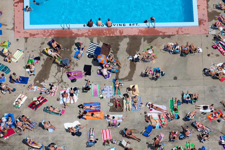 <p>Taken in Boston, this photo of Americans tanning shows how people shape the landscape to their needs.</p>