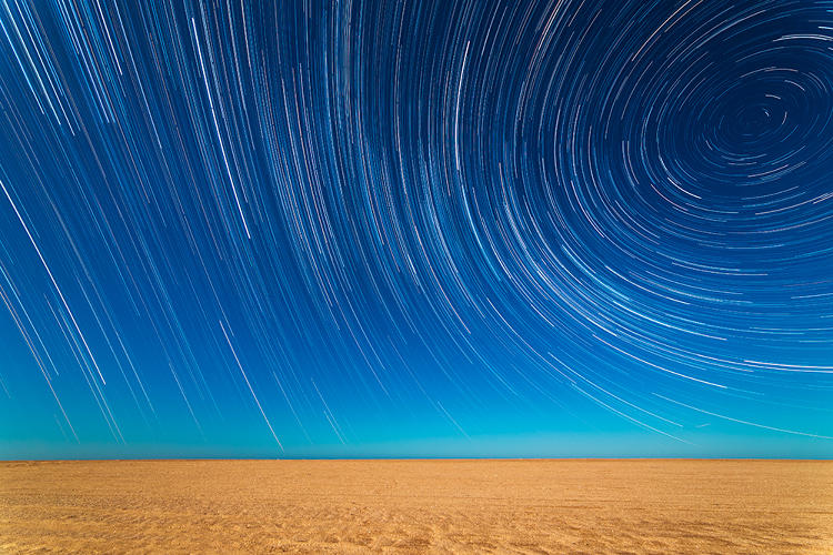 <p>Multiple shots are compiled to create a time-lapse effect, as the Earth's rotation draws the light from the stars into long trails arcing over the beach in Mar de Ajo, Buenos Aires Province, Argentina.</p>