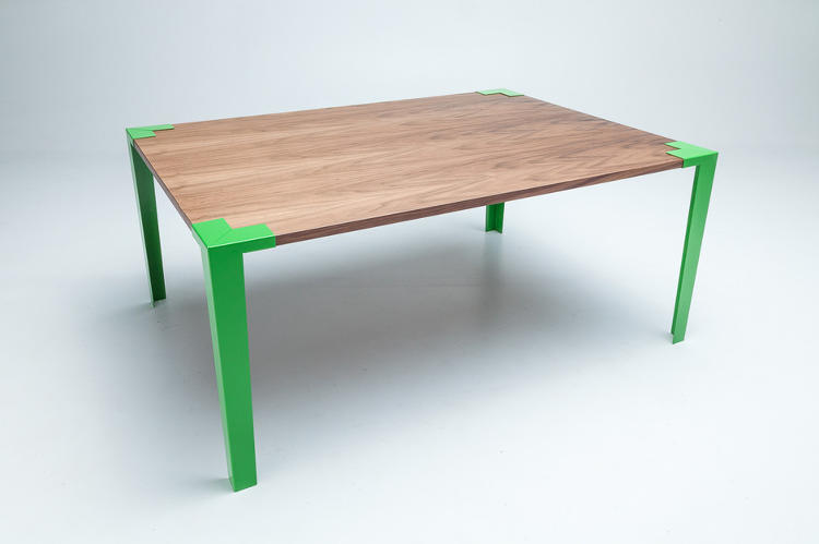 <p>Instead of fasteners and screws that can loosen over time, clamps of solid steel hold the table surface and legs together at four corners. The simple clamps easily snap into place, and their bright colors make them an intentional, attractive part of the design's aesthetic.</p>