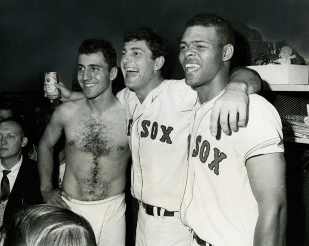 "<p>Can you spot the can of Gansett? It's being gripped by <strong>Carl Yastrzemski</strong>, who has his arms around fellow '67 American League pennant winners <strong>Rico Petrocelli</strong> and <strong>Reggie Smith</strong>. Narragansett was the team's official sponsor in these years, and would sponsor the Red Sox for over 30 years. For a long time, radio broadcasts of Sox games began with ""Hi, Neighbor""--the Narragansett slogan.</p>"
