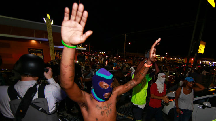 <p>Demonstrators raise their hands during a rally on West Florissant Avenue to protest the shooting death of an unarmed teen by a police officer in Ferguson, Missouri, on August 15, 2014. Eighteen-year-old Michael Brown was shot dead by police in the St. Louis suburb of Ferguson, Missouri on August 09, 2014.</p>