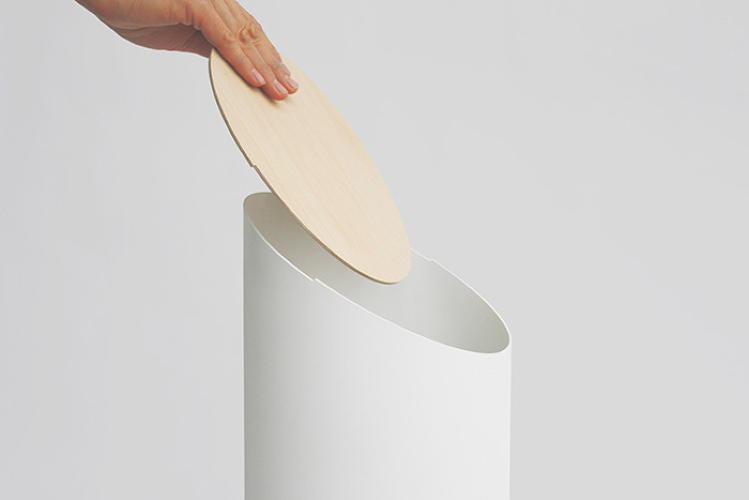 <p>It's also a feat of creative construction. The Swing Bin is not screwed or wired together. It consists of just two parts: a smooth plastic base and a perfectly balanced wooden lid that swings open and shut silently.</p>