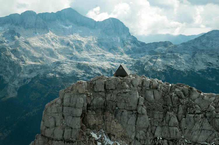 <p>This tiny, stoic A-frame cabin perches atop a rugged landscape in the Julian Alps, 8,303 feet above sea level. It's situated along a summit trail, so hikers and climbers can catch up on rest in the hideout, which sleeps up to nine guests.</p>