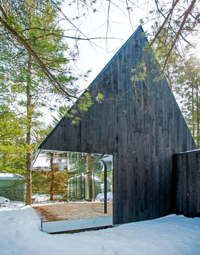 <p>This cottage in an Ontario forest has a mirrored entrance that lets it blend magically into the surrounding wilderness.</p>