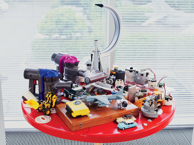 <p>A desk in James Dyson's office displays some of his design inspirations: model cars, electric motors from various Dyson products, and one of the first fans the company made.</p>