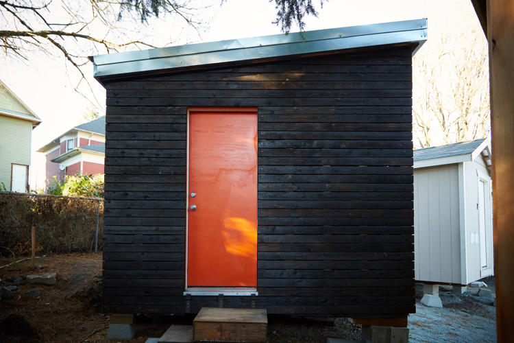 <p>A plot of land that used to hold a single-family house on an average street in Seattle now hosts 14 tiny homes for homeless people.</p>