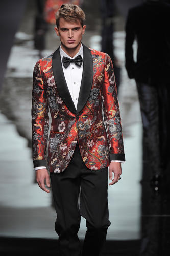 <p>A model displays a tuxedo jacket in red with the &quot;Garden in Hell&quot; textile created by the Chapman Brothers for the Louis Vuitton fall/winter 2013 men's collection.</p>