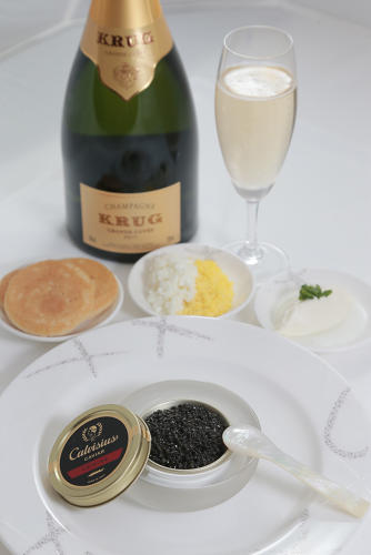 <p>Signature caviar service with crème fraîche, warmed blinis, chopped egg, and a glass of Krug Grande Cuvée champagne—Cathay Pacific</p>